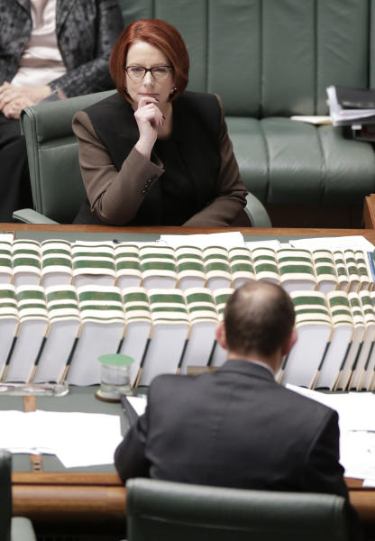 Australian Prime Minister Julia Gillard, top, stares at the opposition leader, Tony Abbott, in Canberra, Australia, Wednesday, June 26, 2013. Opposition leader Abbott challenged Gillard to bring forward the election to Aug. 3 because of the leadership wrangling. (AP Photo/Rick Rycroft)