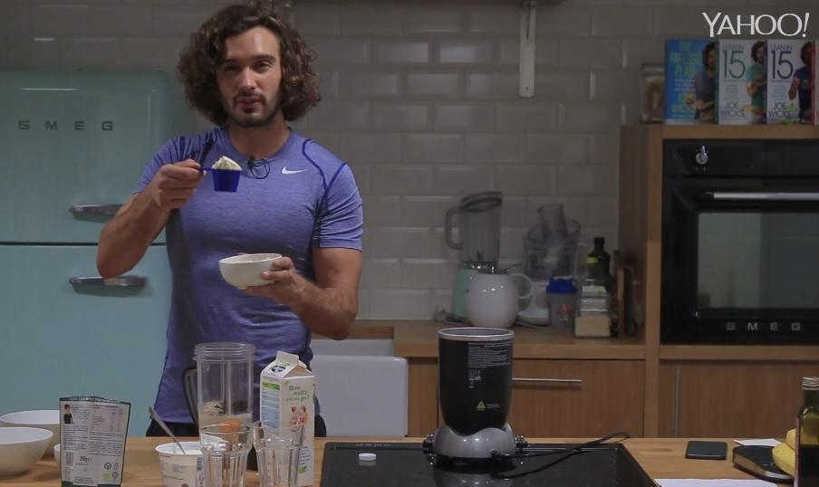 Joe Wicks whisks up a post-workout shake in his kitchen,