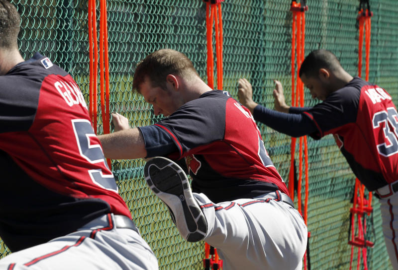 Atlanta Braves pitcher Craig Kimbrel, center, does leg swings during a spring training baseball workout on Sunday, Feb. 16, 2014, in Kissimmee, Fla. The Braves agreed to terms with Kimbrel on a four-year contract. (AP Photo/Alex Brandon)