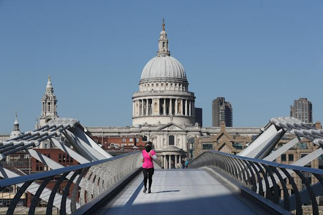 A jogger with their face covered crosses Millenium Bridge in London. (Photo by Jonathan Brady/PA Images via Getty Images)