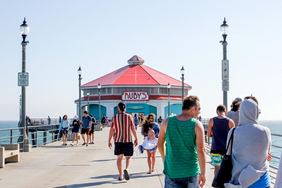 People walk on the Huntington Beach Pier, with Ruby's Diner