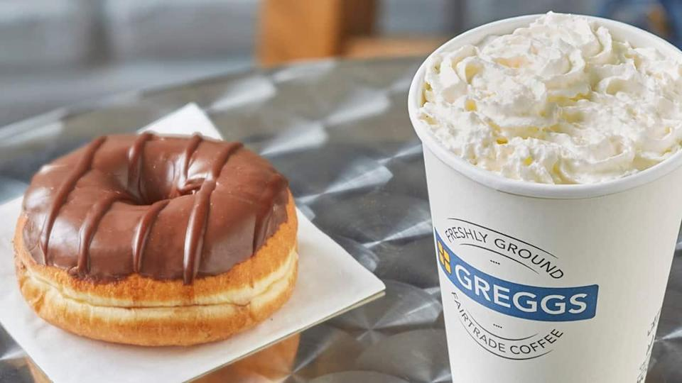 A Greggs doughnut and hot drink sit on a table