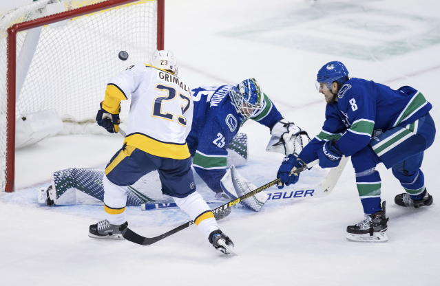 Nashville Predators' Rocco Grimaldi (23) is stopped by Vancouver Canucks goalie Jacob Markstrom, of Sweden, as Canucks' Chris Tanev (8) watches during the second period of an NHL hockey game Thursday, Dec. 6, 2018, in Vancouver, British Columbia. (Darry Dyck/The Canadian Press via AP)