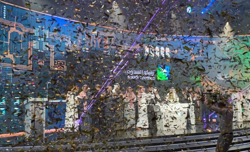 FILE PHOTO: Participants celebrate during the official ceremony marking the debut of Saudi Aramco's IPO on the Riyadh's stock market, in Riyadh
