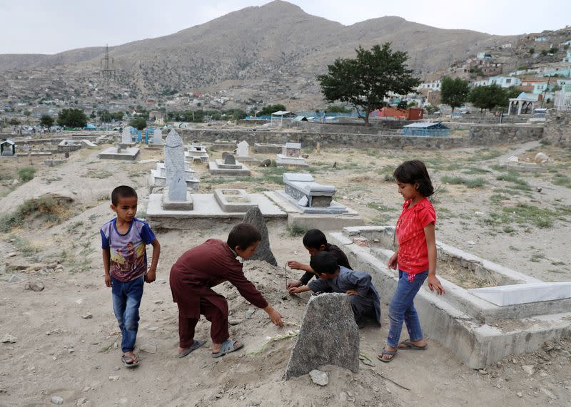 Children put flowers over the grave of twenty-four-year old Fatima Khalil, known as 'Natasha', who was killed in a bomb blast on Saturday, in Kabul