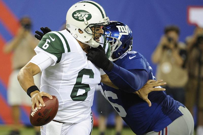 New York Jets quarterback Mark Sanchez (6) is sacked by New York Giants' Marvin Austin (96) during the second half of a preseason NFL football game, Saturday, Aug. 24, 2013, in East Rutherford, N.J. (AP Photo/Bill Kostroun)