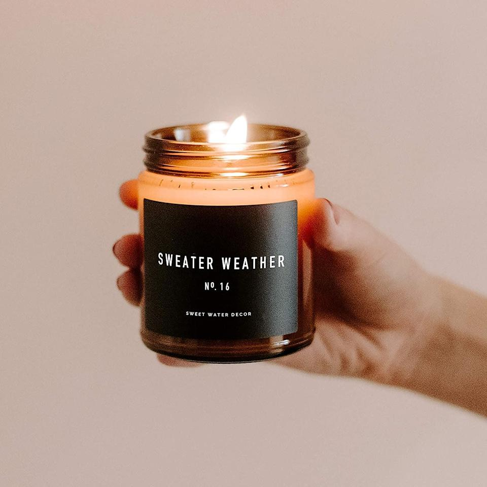 <p>Light up a <span>Sweet Water Decor Sweater Weather Candle </span> ($20) and embrace the cozy vibes of woods, warm spice, and citrus autumn. It has a 40 hour burn time!</p>