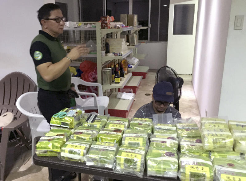"""In this Tuesday, March 19, 2019, photo provided by Philippine Drug Enforcement Agency, PDEA, Aaron Aquino, PDEA Chief, stands next to more than 160 kilos (353 pounds) of methamphetamine concealed in tea wrappers following """"buy-bust"""" raids in Alabang township, Muntinlupa city east of Manila, Philippines. It was PDEA's second largest drug haul this year in a sign of how the problem has persisted despite the president's bloody crackdown on illegal drugs. Aquino said Wednesday, March 20, 2019, three Chinese nationals and a Chinese-Filipino man, who works as an interpreter, were arrested, with the drugs concealed in tea wrappers similar to those seized in Malaysia, Thailand and Myanmar and indicated an international drug syndicate was behind the trafficking. (Sheila Valmoria, Philippine Drug Enforcement Agency PIO via AP)"""