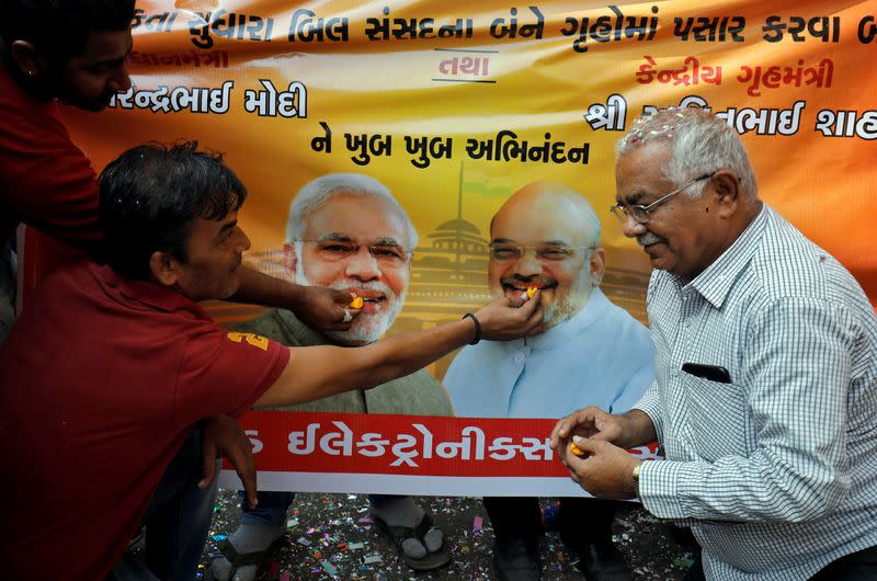 People, who claim to have migrated from Pakistan's Sindh Province, offer sweets to images of India's PM Modi and Home Minister Shah during celebrations after India's parliament passed a Citizenship Amendment Bill, in Ahmedabad