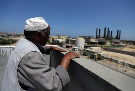 Palestinian man looks out of his house as the Gaza power plant is seen, in the central Gaza Strip