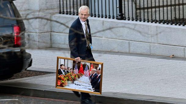 PHOTO: White House advisor Peter Navarro leaves the West Wing of the White House with a photograph of President Donald Trump and Chinese President Xi Jinping in Washington, D.C. on Jan. 13, 2021. (Erin Scott/Reuters)