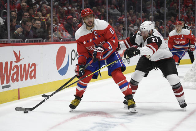 Washington Capitals left wing Alex Ovechkin (8), of Russia, skates with the puck as Arizona Coyotes center Derek Stepan (21) defends during the second period of an NHL hockey game, Monday, Nov. 11, 2019, in Washington. (AP Photo/Nick Wass)