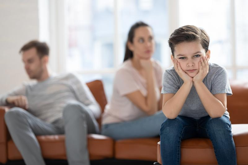 Upset little preschool child boy looking at camera feel sad hurt about parents fights conflicts sit on sofa at home, depressed school kid son suffer from family argument, children and divorce concept