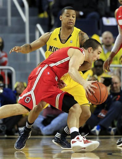 Ohio State guard Aaron Craft drives on Michigan guard Trey Burke, rear, during the first half of an NCAA college basketball game in Ann Arbor, Mich., Saturday, Feb. 18, 2012. (AP Photo/Carlos Osorio)