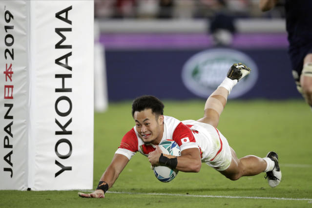 FILE - In this Oct. 13, 2019, file photo, Japan's Kenki Fukuoka scores a try during the Rugby World Cup Pool A game at International Stadium against Scotland in Yokohama, Japan. Japan speedster Fukuoka reportedly will forego the chance to compete in rugby sevens at the postponed Tokyo Olympics in order to pursue a medical career. The Japan Rugby Union announced that Fukuoka had left the national sevens squad. (AP Photo/Jae Hong, File)