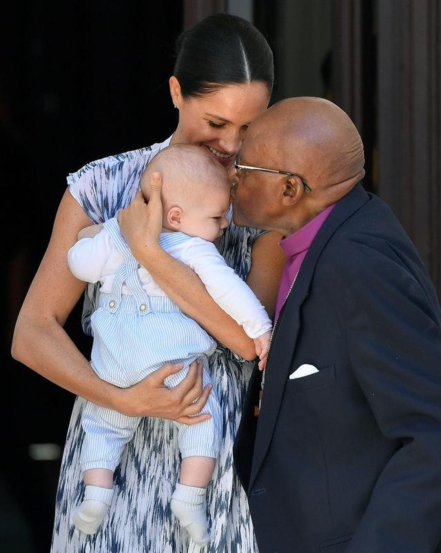 Baby Archie is kissed by Desmond Tutu while in the arms of his mother the Duchess of Sussex, in Cape Town