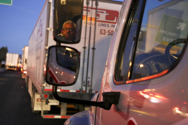 A driver is reflected in the mirror of his truck as he waits to cross the border with the United States in Ciudad Juarez, Mexico, Tuesday, April 9, 2019. Reassignments of border inspectors at land crossings with Mexico have exacerbated wait times for truckers. (AP Photo/Christian Torres)