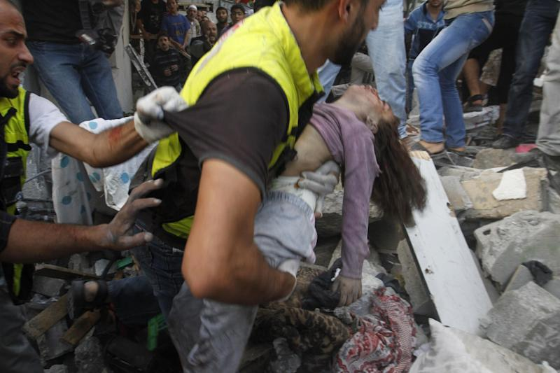 An emergency rescue worker carries a child's body found in the Daloo family house rubble following an Israeli airstrike in Gaza City, Sunday, Nov. 18, 2012. Palestinian medical officials say at least 10 civilians, including women and young children, have been killed in an Israeli airstrike in Gaza City. (AP Photo/Hatem Moussa)