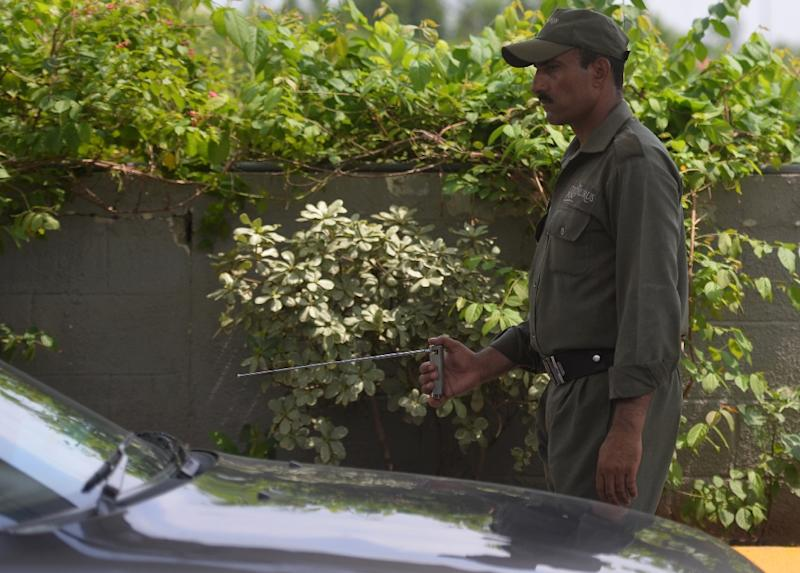 A Pakistani private security guard uses an explosives detector to search a vehicle at a mall entrance in Islamabad on August 1, 2016