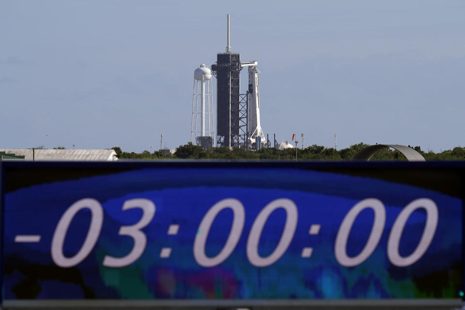 The countdown clock is stopped at a three-hour built in hold as a SpaceX Falcon 9 rocket, with the company's Crew Dragon capsule attached, sits on the launch pad at Launch Complex 39A Sunday, Nov. 15, 2020, at the Kennedy Space Center in Cape Canaveral, Fla. Four astronauts will fly on the SpaceX Crew-1 mission to the International Space Station scheduled for launch on later today. (AP Photo/Chris O'Meara)