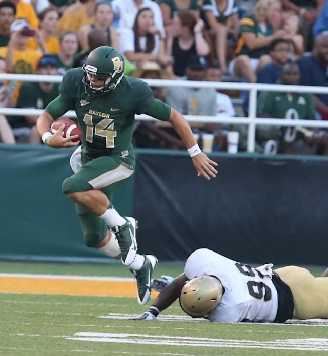 Baylor quarterback Bryce Petty (14), left, slips past Wofford's defensive end Tarek Odom (99), right, during the first half of an NCAA college football game on Saturday, Aug. 31, 2013, in Waco, Texas. (AP Photo/Waco Tribune Herald, Rod Aydelotte)