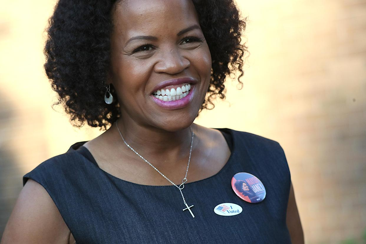 Acting Mayor Kim Janey smiles while wearing a campain pin next to an