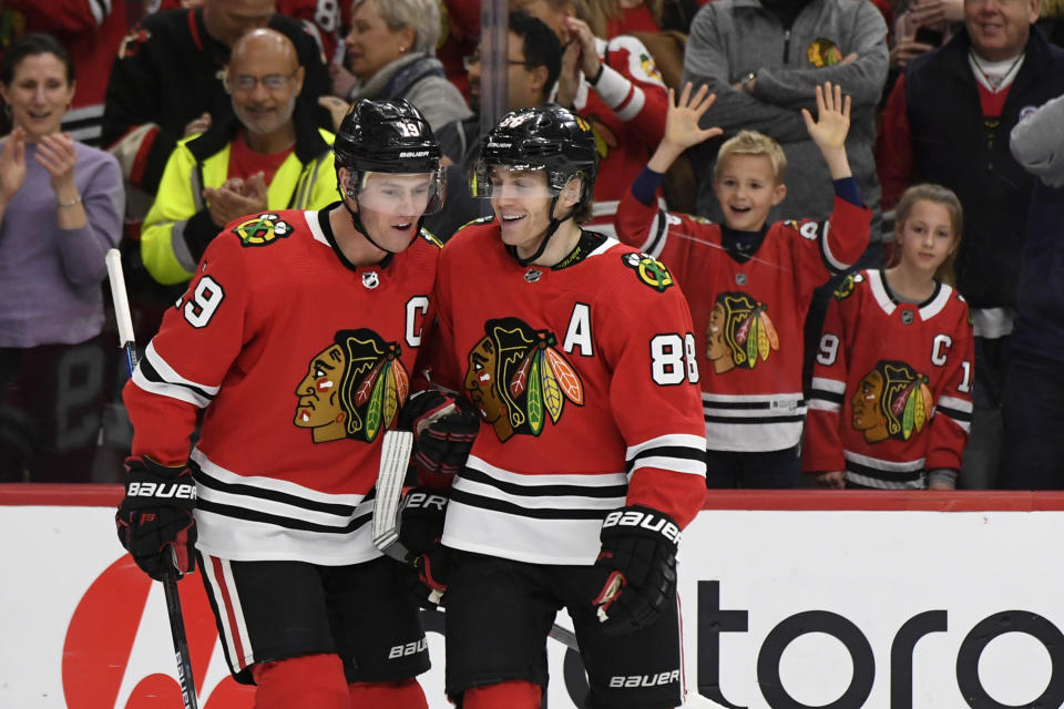 FILE - In this Dec. 15, 2019, file photo, Chicago Blackhawks' Patrick Kane (88) celebrates with teammate Jonathan Toews (19) after scoring his third goal of the game in the third period of an NHL hockey game against the Minnesota Wild in Chicago. (AP Photo/Paul Beaty, File)