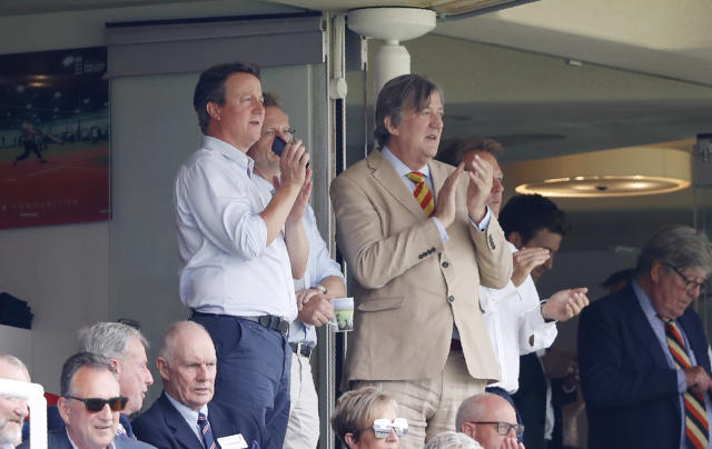 Former British Prime Minister David Cameron, left with TV personality and writer Stephen Fry watch the Cricket World Cup match between England and Australia at Lord's cricket ground in London, Tuesday, June 25, 2019. (AP Photo/Alastair Grant)