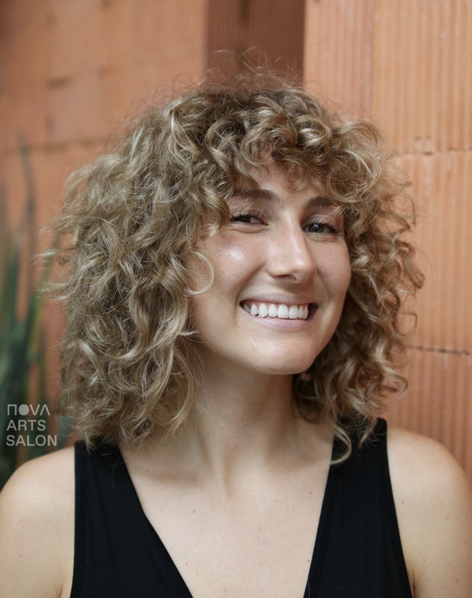 """The trick for nailing this cut with curls is making sure your stylist specializes in curly hair. (The <a href=""""https://swivelbeauty.com/"""" rel=""""nofollow noopener"""" target=""""_blank"""" data-ylk=""""slk:Swivel app"""" class=""""link rapid-noclick-resp"""">Swivel app</a> is a great resource for finding curl and coil experts in your area.) A cute pair of bangs also help."""