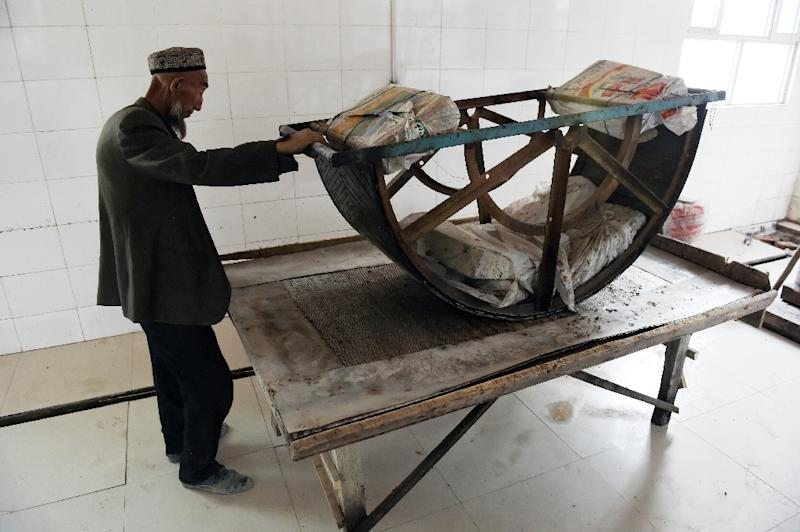 Caretaker Iburamzi Emin demonstrates the use of a traditional wine press at an Uighur-owned winery in Awat, China's western Xinjiang region (AFP Photo/Greg Baker)