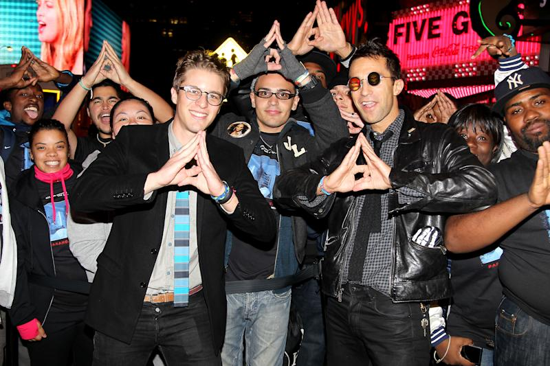 "This Oct. 16, 2012 photo released by Starpix shows directors Henry Joost, foreground left, and Ariel Schulman, with sunglasses, posing with fans at a screening for their film, ""Paranormal Activity 4,"" at Regal E-Walk Stadium 13 in New York. (AP Photo/Starpix, Dave Allocca)"