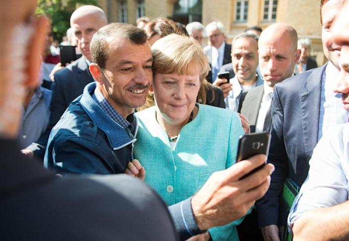 Asylum seeker takes a selfie picture with German Chancellor Angela Merkel following Merkel's visit at a branch of the Federal Office for Migration and Refugees and a camp for asylum-seekers in Berlin on September 10, 2015 (AFP Photo/Bernd Von Jutrczenka)