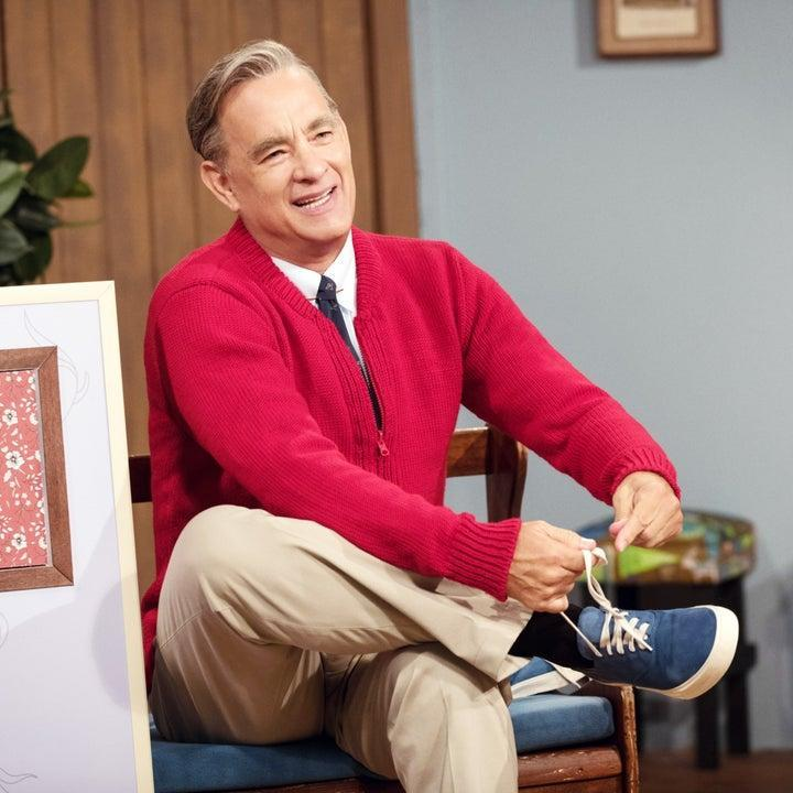Fred Rogers dressed in sneakers, pants, a shirt and tie, and a sweater in A Beautiful Day in the Neighborhood