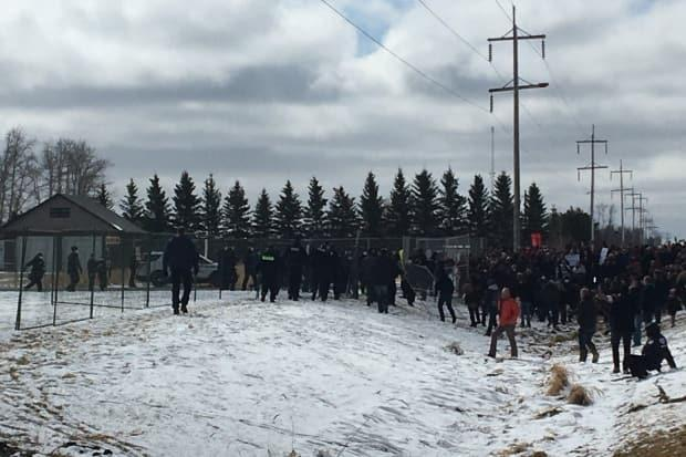A portion of the fence was briefly taken down by some of the crowd before being restored. (Jordan Omstead/CBC - image credit)