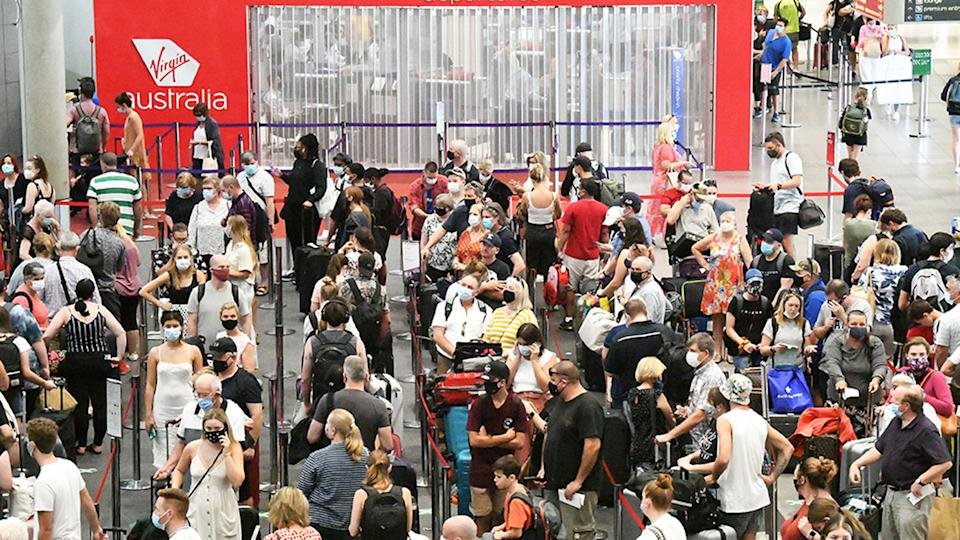 Passengers check in for flights out of Brisbane, ahead of Greater Brisbane's three-day coronavirus lockdown. Source: AAP