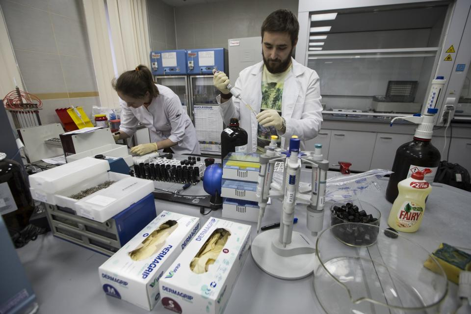 FILE - In this May 24, 2016 file photo, employees Natalya Bochkaryova, left, and Ilya Podolsky work at the Russia's national drug-testing laboratory in Moscow, Russia. Russia is accused of manipulating an archive of doping data from a laboratory in Moscow, which was meant to be a peace offering to the World Anti-Doping Agency to solve earlier disputes. (AP Photo/Alexander Zemlianichenko, file)