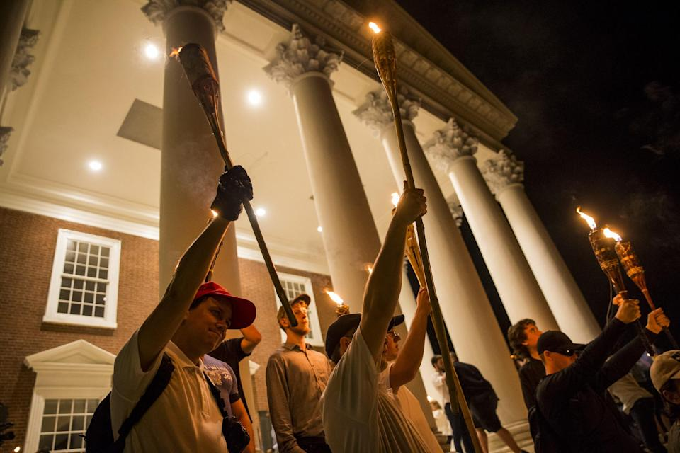<p>Young men hold up torches on the steps of the Rotunda as other Neo Nazis, Alt-Right, and White Supremacists march through the University of Virginia Campus with torches in Charlottesville, Va., on Aug. 11, 2017. (Photo: Samuel Corum/Anadolu Agency/Getty Images) </p>
