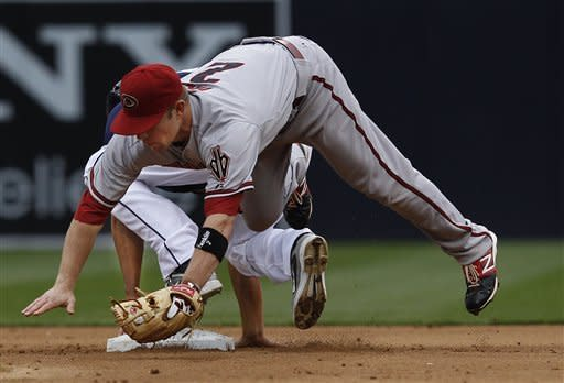 Arizona Diamondbacks second baseman Aaron Hill, top, tumbles over San Diego Padres' Will Venable while catching an errant throw during Venable's stolen base in the fourth inning of a baseball game on Saturday, June 2, 2012, in San Diego. (AP Photo/Lenny Ignelzi)