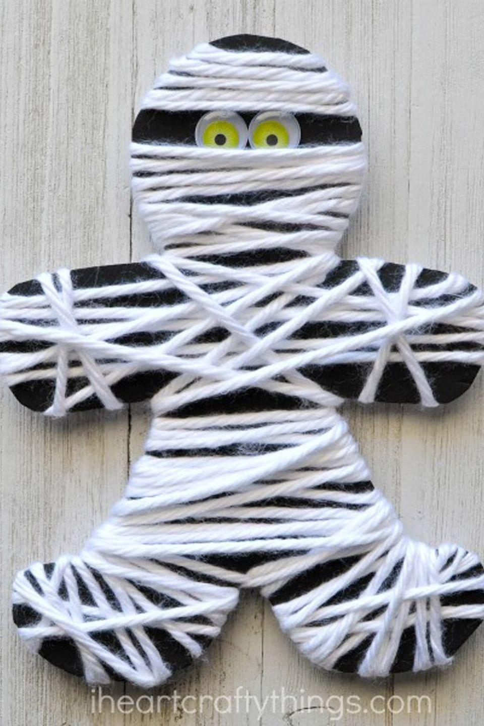 """<p>The only skill required for this cute mummy craft is to wrap string around a paper doll figure. The best part is, no matter which direction it goes, it will always be right! String together multiples for a creative garland.</p><p><strong>Get the tutorial at <a href=""""https://iheartcraftythings.com/yarn-wrapped-mummy-craft.html"""" rel=""""nofollow noopener"""" target=""""_blank"""" data-ylk=""""slk:I Heart Crafty Things"""" class=""""link rapid-noclick-resp"""">I Heart Crafty Things</a>.</strong> </p>"""