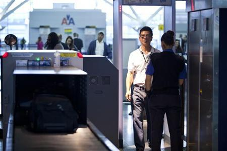A traveler walks through a metal detector at a security check point in John F. Kennedy Airport in New York, February, 29, 2012. REUTERS/Andrew Burton