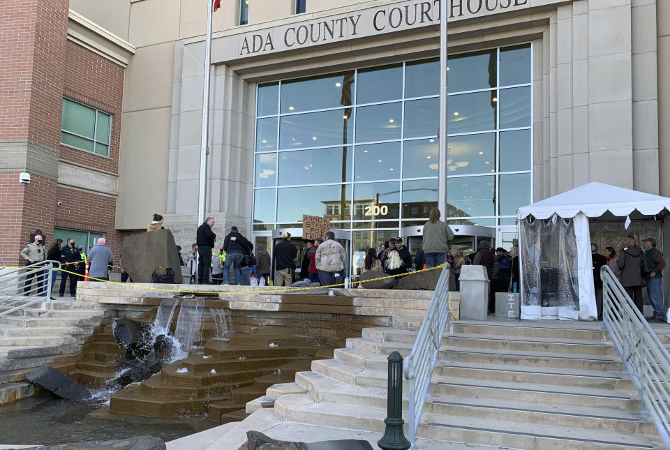 Roughly two dozen people gather outside the Ada County Courthouse in Boise, Idaho Monday, March 15, 2021, to protest mask rules and other measures taken to slow the coronavirus pandemic and to show support for fellow protester and anti-government activist Ammon Bundy. Bundy was scheduled to stand trial on charges that he trespassed and obstructed officers at the Idaho Statehouse during a special legislative session last fall, but Magistrate Judge David Manweiler issued a warrant for Bundy's arrest after Bundy failed to appear in the courtroom. Bundy was arrested late Monday morning on a misdemeanor charge of failing to appear in court. (AP Photo/Rebecca Boone)