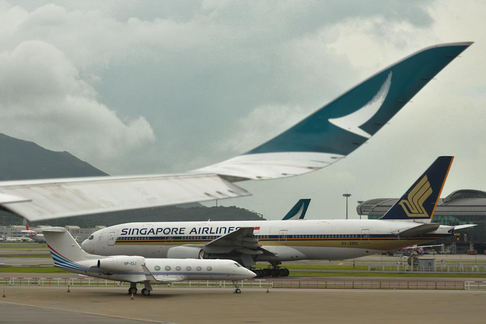 Planes belonging to Singapore Airlines, and the Hong Kong Airline Carrier Cathay Pacific, seen at Hong Kong International Airport in Hong Kong, China.  On Wednesday, July 3, 2019, in Hong Kong, China. (Photo by Artur Widak/NurPhoto via Getty Images)