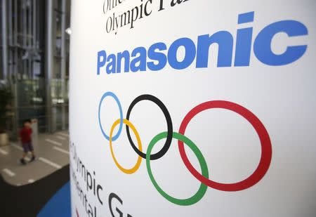 A Panasonic Corp logo and an Olympic symbol are seen as a kid walks past at Panasonic centre in Tokyo