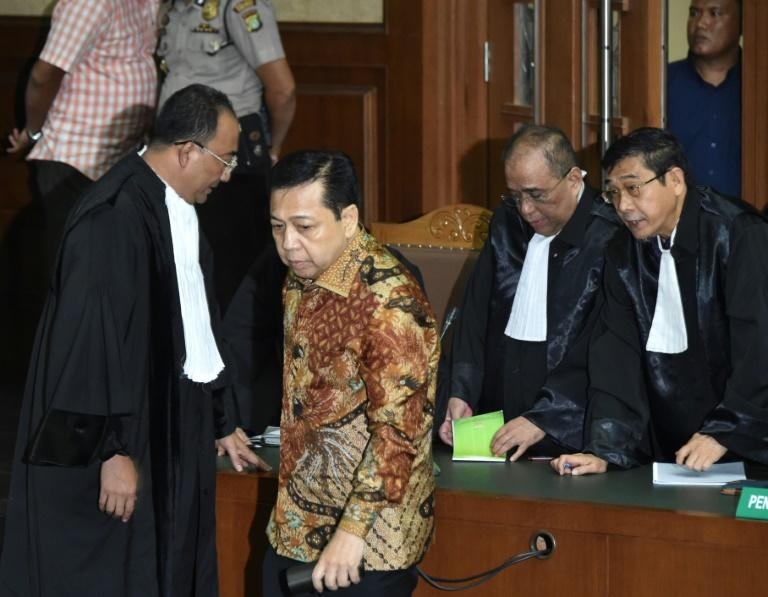 Indonesia's former house speaker Setya Novanto (2nd L) was hit with one of the country's heaviest sentences for corruption
