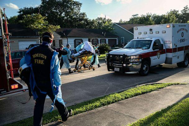 PHOTO: Houston Fire Department EMS medics transport a man with possible COVID-19 symptoms to a hospital, on Aug. 10, 2020, in Houston. (John Moore/Getty Images)