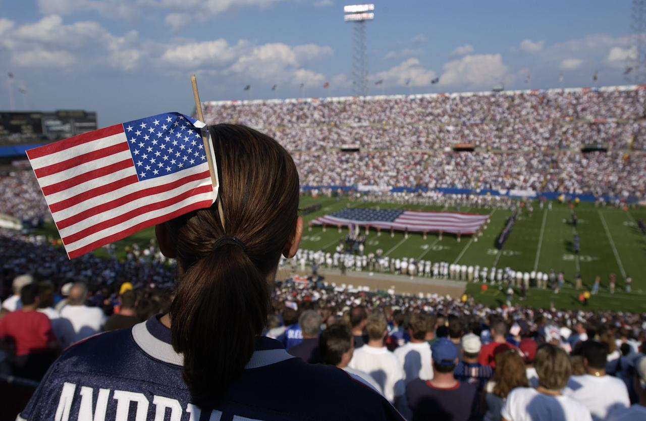 A New England Patriot fan wears an American flag in her hair during a pregame ceremony honoring those fallen in the World Trade Center tragedy prior to the game against the New York Jets at Foxboro Stadium in Foxboro, Massachusetts. The Jets won 10-3. DIGITAL IMAGE. Mandatory Credit: Ezra Shaw/ALLSPORT
