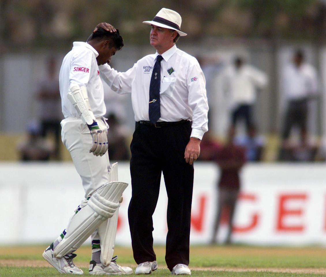 22 Sep 1999:  Chaminda Vaas of Sri Lanka has his head inspected by umpire Doug Cowie of New Zealand after being struck off the bowling of Glenn McGrath, during day one of the second test between Sri Lanka and Australia at Galle International Stadium, Galle, Sri Lanka.X Mandatory Credit: Hamish Blair/ALLSPORT