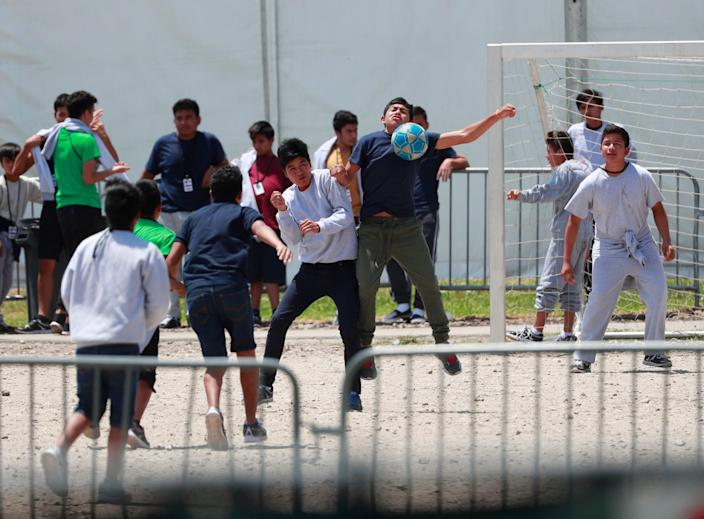 In this April 19, 2019 file photo, migrant children play soccer at the Homestead Temporary Shelter for Unaccompanied Children on Good Friday in Homestead, Fla. The government has stopped reimbursing some contracted shelters for the cost of teaching immigrant children English-language courses and providing legal services and recreational activities. (AP Photo/Wilfredo Lee, File)