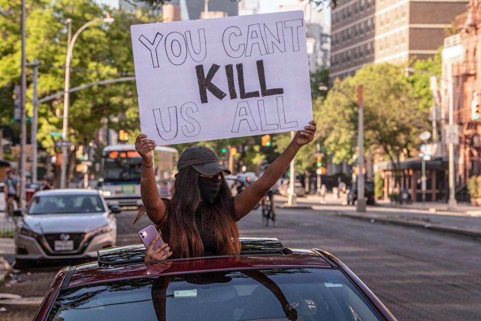 "<p>A woman holds a sign reading, ""You can't kill us all"" as she puts her head out of the roof deck of a car.</p>"