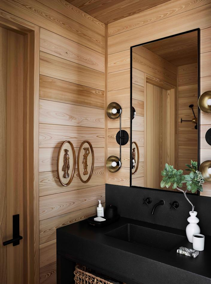 In the changing room, a custom cast-concrete vanity reflects the surrounding landscape through its jet-black color, while the top-to-bottom cypress planks provide a counterpoint of warmth and an essential function—the wood is mildew-resistant, a no-brainer for shoreline haunt.